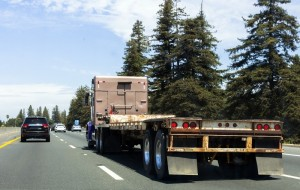 Semi truck on highway with empty flatbed trailer.